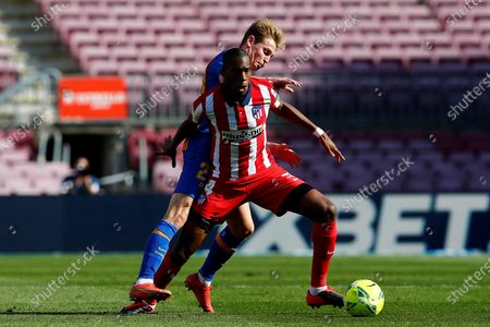 Stock Photo of FC Barcelona's midfielder Frenkie De Jong (L) vies for the ball against Atletico's midfielder Geoffrey Kondogbia (R) during the Spanish LaLiga soccer match between FC Barcelona and Atletico de Madrid at Camp Nou stadium in Barcelona, Catalonia, Spain, 08 May 2021.