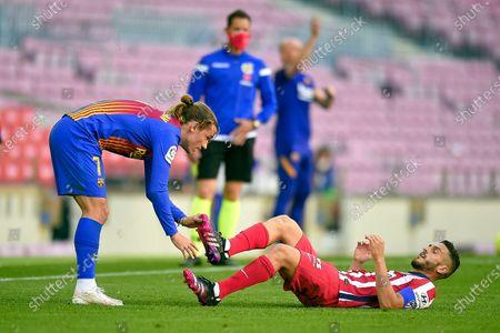 Antoine Griezmann of FC Barcelona helps Koke Resurreccion of Atletico de Madrid