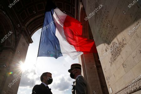 French President Emmanuel Macron, left, talks to Gen. Francois Lecointre during a ceremony at the Arc de Triomphe to mark the 76th anniversary of the end of World War II, in Paris
