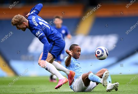 Chelsea's Timo Werner, left, and Manchester City's Raheem Sterling challenge for the ball during the English Premier League soccer match between Manchester City and Chelsea at the Etihad Stadium in Manchester