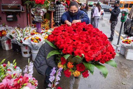 Elizabeth Rodriguez arranges 100 red roses for a customer as colleague Angel Bernabe holds them in place outside of Pariso Floral flower shop on 8th St. in the flower district section of downtown Los Angeles. Florists warn of flower shortage ahead of Mother's Day (Mel Melcon / Los Angeles Times)