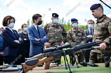 French Defense Minister Florence Parly and French Secretary of State and Government's spokesperson Gabriel Attal listen to explanations on a gun during a visit to the military camp of Satory in Versailles-Satory, west of Paris