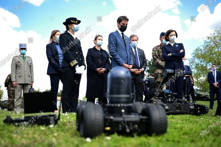 French Defense Minister Florence Parly, right, and French Secretary of State and Government's spokesperson Gabriel Attal, center, listen to explanations on a gun during a visit to the military camp of Satory in Versailles-Satory, west of Paris