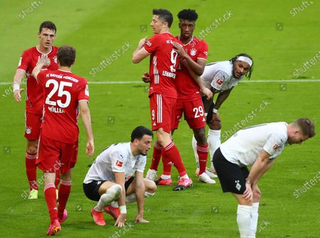 Bayern's Kingsley Coman, centre right, celebrates with Bayern's Robert Lewandowski after scoring his side's fourth goal during the German Bundesliga soccer match between Bayern Munich and Borussia Moenchengladbach at the Allianz Arena stadium in Munich, Germany
