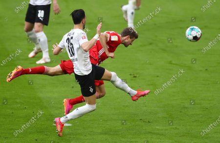Moenchengladbach's Ramy Bensebaini, left, and Bayern's Thomas Mueller challenge for the ball during the German Bundesliga soccer match between Bayern Munich and Borussia Moenchengladbach at the Allianz Arena stadium in Munich, Germany