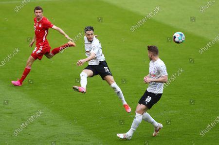 Bayern's Thomas Mueller, centre, kicks the ball during the German Bundesliga soccer match between Bayern Munich and Borussia Moenchengladbach at the Allianz Arena stadium in Munich, Germany