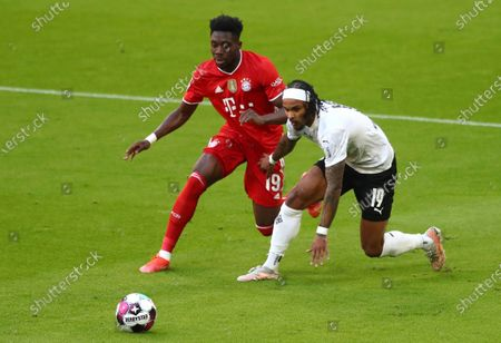 Bayern's Alphonso Davies, left, and Moenchengladbach's Valentino Lazaro challenge for the ball during the German Bundesliga soccer match between Bayern Munich and Borussia Moenchengladbach at the Allianz Arena stadium in Munich, Germany