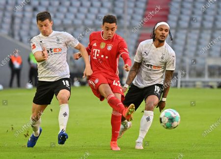 Stock Photo of Bayern's Jamal Musiala, centre, kicks the ball ahead of Moenchengladbach's Stefan Lainer, left, and Moenchengladbach's Valentino Lazaro during the German Bundesliga soccer match between Bayern Munich and Borussia Moenchengladbach at the Allianz Arena stadium in Munich, Germany
