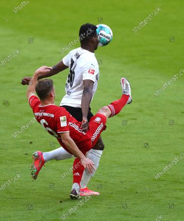 Bayern's Joshua Kimmich, left, and Moenchengladbach's Breel Embolo challenge for the ball during the German Bundesliga soccer match between Bayern Munich and Borussia Moenchengladbach at the Allianz Arena stadium in Munich, Germany