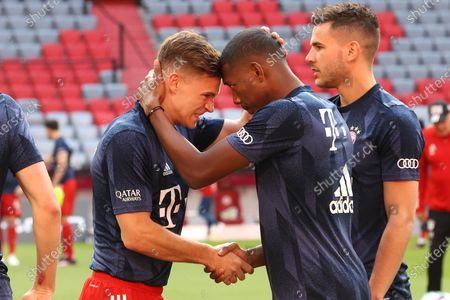 Joshua Kimmich (L) and David Alaba of FC Bayern Muenchen interact during the warm up prior to the Bundesliga match between FC Bayern Muenchen and Borussia Moenchengladbach at Allianz Arena in Munich, Germany, 08 May 2021.