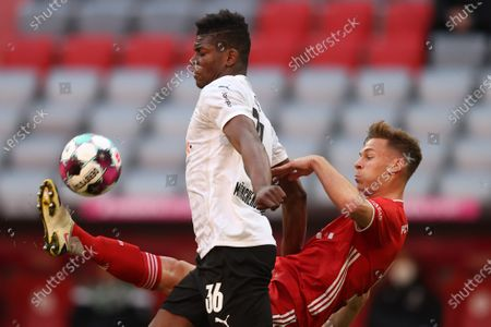 Breel Embolo of Borussia Moenchengladbach battles for possession with Joshua Kimmich of FC Bayern Muenchen (R) during the Bundesliga match between FC Bayern Muenchen and Borussia Moenchengladbach at Allianz Arena in Munich, Germany, 08 May 2021.