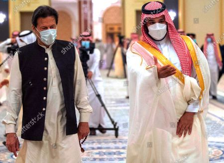 In this photo released by Saudi Royal Palace, Saudi Crown Prince Mohammed bin Salman, right, greets Pakistan's Prime Minister Imran Khan, before signing cooperation agreements at the royal palace in Jiddah, Saudi Arabia