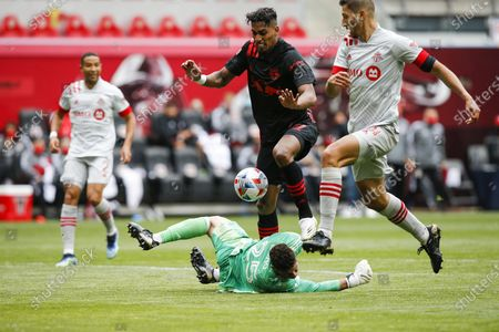 New York Red Bulls attacker Fabio, center, fights for the ball against Toronto FC defender Omar Gonzalez, right, and goalkeeper Alex Bono during an MLS soccer match, at Red Bull Arena in Harrison, NJ