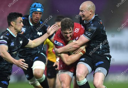 Angus O'Brien of Scarlets is tackled by Luke Price and Matthew Aubrey of Ospreys.