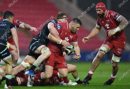 Rob Evans of Scarlets is tackled by Sam Cross of Ospreys.