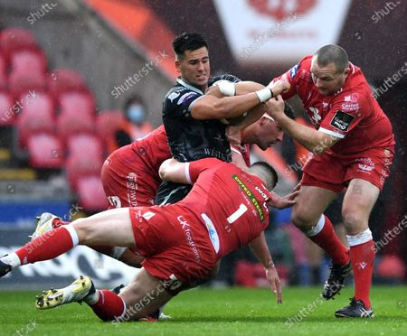 Tiaan Thomas-Wheeler of Ospreys is tackled by Rob Evans and Ken Owens of Scarlets.