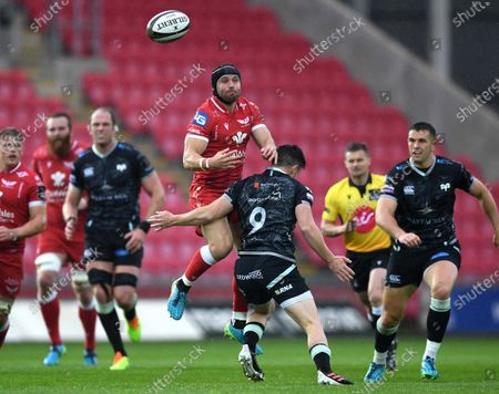 Leigh Halfpenny of Scarlets goes up for high ball as Matthew Aubrey of Ospreys tackles.