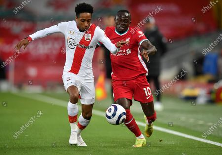 Southampton's Kyle Walker-Peters, left, duels for the ball with Liverpool's Sadio Mane during the English Premier League soccer match between Liverpool and Southampton at Anfield stadium in Liverpool, England