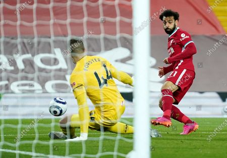 Southampton's goalkeeper Fraser Forster, left, makes a save in front of Liverpool's Mohamed Salah during the English Premier League soccer match between Liverpool and Southampton at Anfield stadium in Liverpool, England