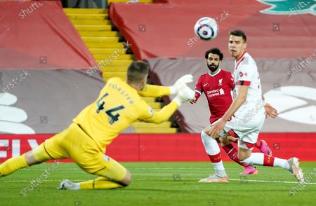 Southampton's goalkeeper Fraser Forster, left, makes a save in front of Liverpool's Mohamed Salah, center, during the English Premier League soccer match between Liverpool and Southampton at Anfield stadium in Liverpool, England