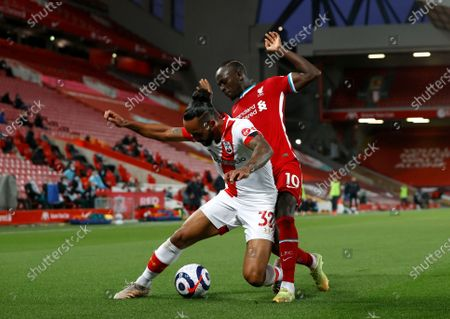 Southampton's Theo Walcott, left, duels for the ball with Liverpool's Sadio Mane during the English Premier League soccer match between Liverpool and Southampton at Anfield stadium in Liverpool, England