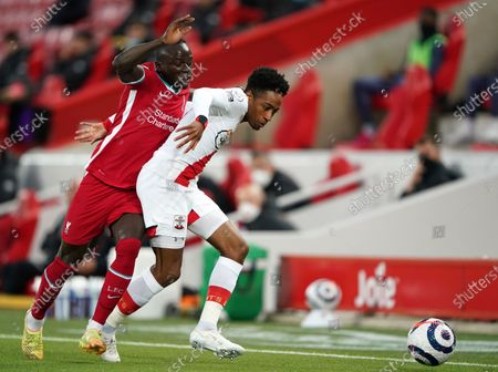 Liverpool's Sadio Mane, left, duels for the ball with Southampton's Kyle Walker-Peters during the English Premier League soccer match between Liverpool and Southampton at Anfield stadium in Liverpool, England