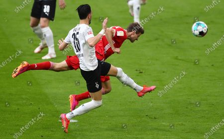 Moenchengladbach's Ramy Bensebaini (L) in action against Bayern's Thomas Mueller (R) during  the German Bundesliga soccer match between FC Bayern Munich and Borussia Moenchengladbach in Munich, Germany, 08 May 2021.