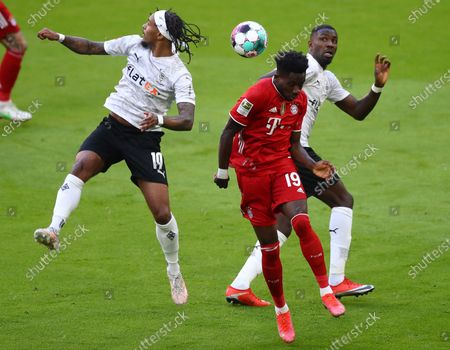 Moenchengladbach's Valentino Lazaro (L) in action against Bayern's Alphonso Davies (C)  during  the German Bundesliga soccer match between FC Bayern Munich and Borussia Moenchengladbach in Munich, Germany, 08 May 2021.
