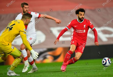 Liverpool's Mohamed Salah (R) tried to pass by Southampton's goalkeeper Fraser Forster (L) during the English Premier League soccer match between Liverpool FC and Southampton FC in Liverpool, Britain, 08 May 2021.