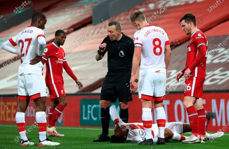 Southampton's Kyle Walker-Peters lays down injured as main referee Kevin Friend asks for assistance during the English Premier League soccer match between Liverpool FC and Southampton FC in Liverpool, Britain, 08 May 2021.
