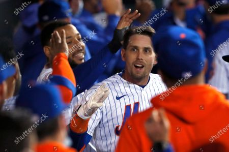 New York Mets' Jeff McNeil celebrates in the dugout after hitting a home run against the Arizona Diamondbacks during the third inning of a baseball game, in New York
