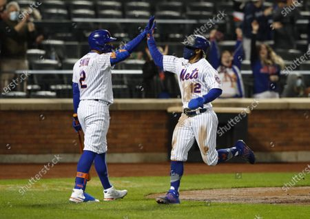 New York Mets' Francisco Lindor (12) is congratulated by Dominic Smith (2) after scoring against the Arizona Diamondbacks during the third inning of a baseball game, in New York