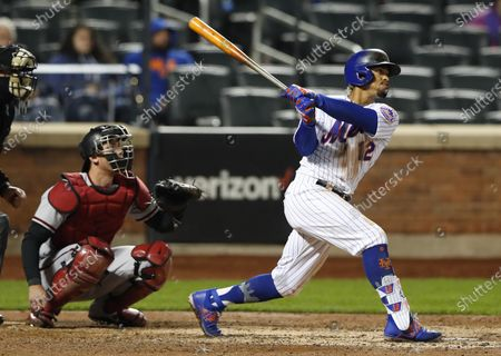 New York Mets' Francisco Lindor follows through on a double against the Arizona Diamondbacks during the fifth inning of a baseball game, in New York