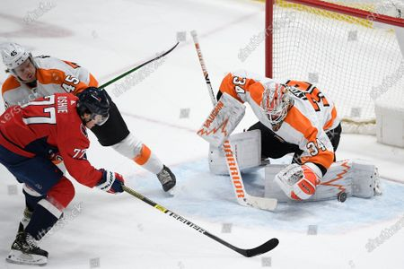 Philadelphia Flyers goaltender Alex Lyon (34) stops the puck against Washington Capitals right wing T.J. Oshie (77) during the second period of an NHL hockey game, in Washington. Flyers defenseman Cam York is at top left