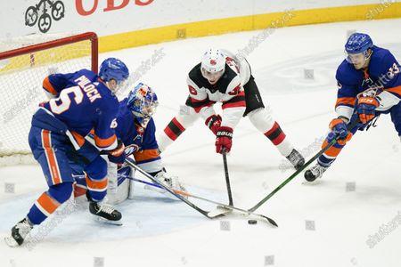 New York Islanders' Ryan Pulock (6) Mathew Barzal (13) and goaltender Ilya Sorokin (30) defend the net from New Jersey Devils' Jack Hughes (86) during the third period of an NHL hockey game, in Uniondale, N.Y. The Islanders won 5-1