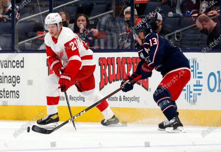 Detroit Red Wings defenseman Dennis Cholowski, left, passes the puck in front of Columbus Blue Jackets forward Cam Atkinson during the first period of an NHL hockey game in Columbus, Ohio