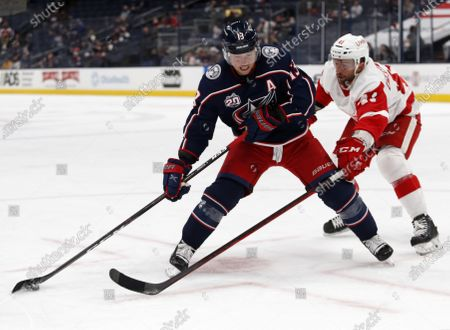 Columbus Blue Jackets forward Cam Atkinson, left, controls the puck in front of Detroit Red Wings forward Luke Glendening during the second period of an NHL hockey game in Columbus, Ohio