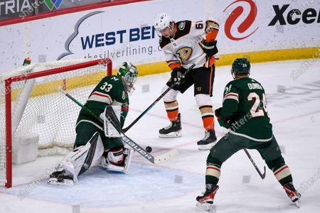 Minnesota Wild goalie Cam Talbot, left, stops a shot by Anaheim Ducks right wing Troy Terry, center, as Wild defenseman Matt Dumba watches during overtime of an NHL hockey game, in St. Paul, Minn. The Wild won 4-3