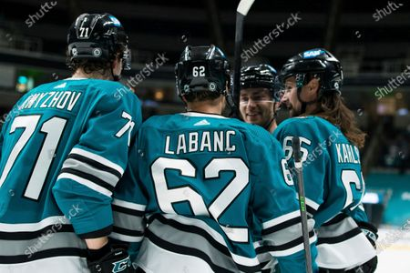 San Jose Sharks right wing Kevin Labanc (62) celebrates with defenseman Nikolai Knyzhov (71) and defenseman Erik Karlsson (65) after scoring a goal against the Arizona Coyotes during the first period of an NHL hockey game in San Jose, Calif