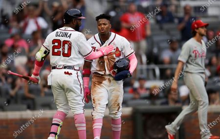 Atlanta Braves' Marcell Ozuna (20) congratulates Ronald Acuna Jr. after Acuna scored against the Philadelphia Phillies in the first inning of a baseball game, in Atlanta