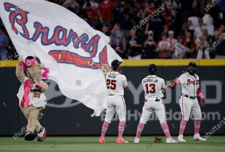 Atlanta Braves outfielders Cristian Pache (25), Ronald Acuna Jr. (13) and Marcell Ozuna, right, celebrate the team's 6-1 victory over the Philadelphia Phillies at the end of a baseball game, in Atlanta