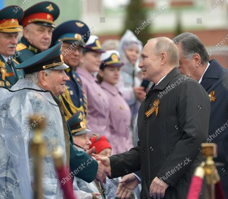 Russian President Vladimir Putin (front R) and Tajik President Emomali Rahmon (back R, partly seen) greet veterans as they arrive for the Victory Day military parade in the Red Square in Moscow, Russia, 09 May 2021. Russia holds its Victory Day parade annually on 09 May to mark the surrender of Nazi Germany in 1945.