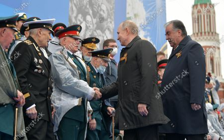 Russian President Vladimir Putin (2-R) and Tajik President Emomali Rahmon (R) greet military veterans as they arrive for the Victory Day military parade in the Red Square in Moscow, Russia, 09 May 2021. Russia holds its Victory Day parade annually on 09 May to mark the surrender of Nazi Germany in 1945.
