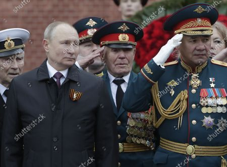 Stock Photo of Russian President Vladimir Putin (front L) and Russian Defense Minister Sergei Shoigu (R) attend a wreath laying ceremony at the Tomb of the Unknown Soldier near the Kremlin wall after the Victory Day military parade in the Red Square in Moscow, Russia, 09 May 2021. Russia holds its Victory Day parade annually on 09 May to mark the surrender of Nazi Germany in 1945.