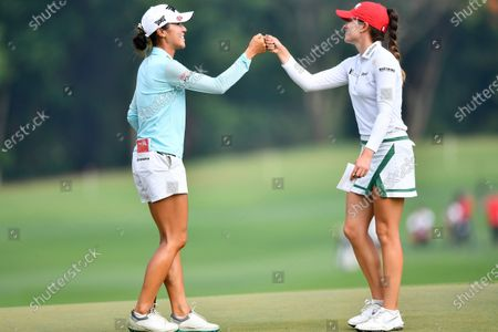 Lydia Ko of New Zealand, left, and Gaby Lopez of Mexico touch their hands after finishing their play on the 18th hole during the final round of the LPGA Honda Thailand golf tournament in Pattaya, southern Thailand