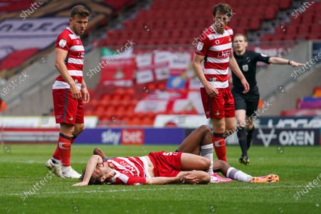 Stock Photo of Doncaster Rovers defender Joe Wright (5) gestures and reacts down injured during the EFL Sky Bet League 1 match between Doncaster Rovers and Peterborough United at the Keepmoat Stadium, Doncaster