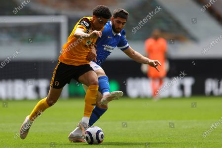 Wolverhampton Wanderers' Ki-Jana Hoever, left, is challenged by Brighton's Alireza Jahanbakhsh during the English Premier League soccer match between Wolverhampton Wanderers and Brighton & Hove Albion at the Molineux Stadium in Wolverhampton, England