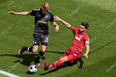 Freiburg's Philipp Lienhart (L) in action against Cologne's Jonas Hector (R) during the German Bundesliga soccer match between 1. FC Koeln and SC Freiburg in Cologne, Germany, 09 May 2021.