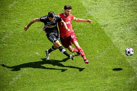 Freiburg's Vincenzo Grifo (L) in action against Cologne's Jonas Hector (R) during the German Bundesliga soccer match between 1. FC Koeln and SC Freiburg in Cologne, Germany, 09 May 2021.
