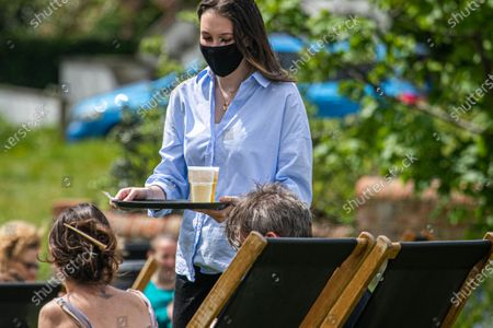 People drinking outdoors in a pub garden in Wimbledon Common, South West London  on Sunday as lockdown restrictions are lifted as weather forecasters predict warmer weather with temperatures rising over 20c on Sunday
